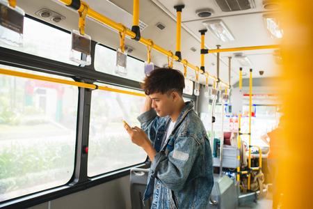 Handsome asian man sitting in city bus and typing a message on the phone. Banque d'images