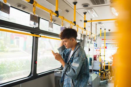 Knappe Aziatische man zit in stadsbus en typt een bericht op de telefoon. Stockfoto
