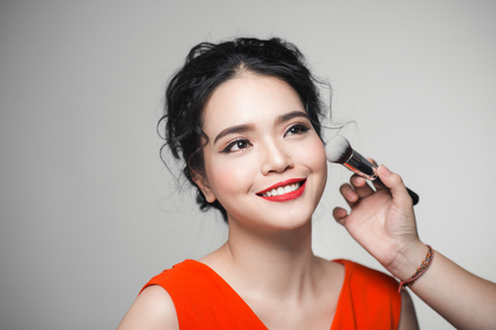 Portrait of attractive asian young adult woman applying blusher Фото со стока