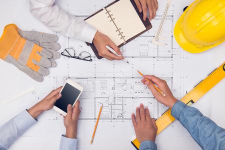 Handen van professionele architecten die discussiëren en werken met blauwdrukken Stockfoto - 83404277