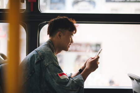 Handsome asian man sitting in city bus and typing a message on the phone. Фото со стока