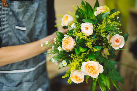 Male florist making beautiful bouquet at flower shop Stok Fotoğraf