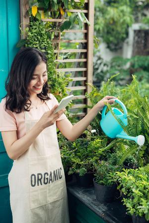 여름에 그녀의 정원에서 꽃을 급수 아시아 여자 정원사