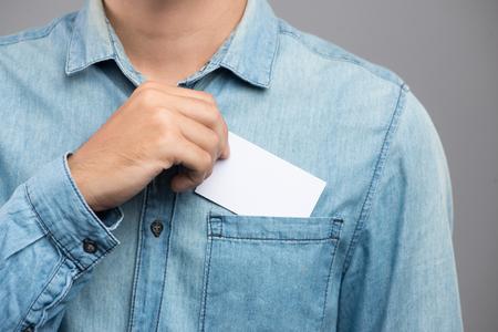 Jeune homme qui sort une carte de visite vierge de la poche de sa chemise Banque d'images - 83546767