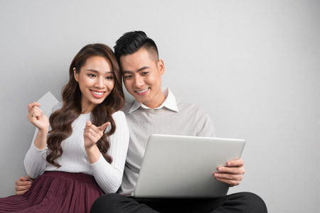 Young attractive and nice happy couple online shopping with credit card and computer laptop sitting on floor.