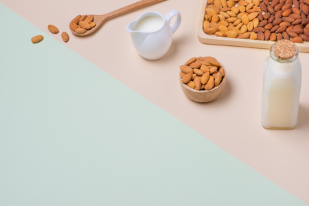 Almonds and milk bottle on light background. Almond nuts in spoon. Stock fotó