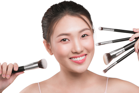 A portrait of young pretty isolated on white background women holding makeup brushes