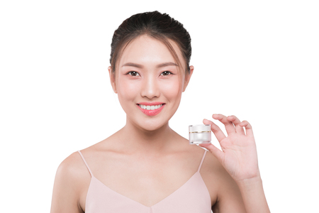 Portrait of beautiful smiling girl with cream bottle in hand. Skin care product