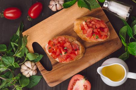 Bruschetta appétissante italienne simple à la tomate, sur une table en bois Banque d'images - 83546925