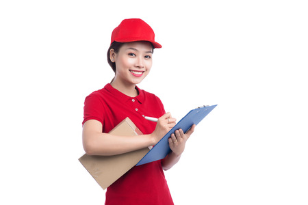 Beautiful young delivery woman in red t-shirt and cap smiling, holding a folder and making notes, on white background Stok Fotoğraf