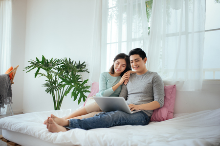 Attractive young asian adult couple looking laptop sitting on bed