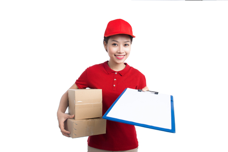 Beautiful young delivery woman in red t-shirt and cap smiling, holding a folder and making notes, on white background Stock Photo