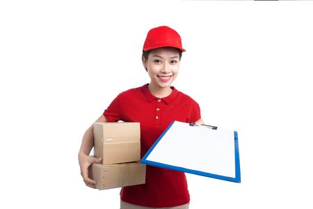 Mooie jonge leveringsvrouw in rode t-shirt en GLB die, een omslag en het maken van nota's, op witte achtergrond glimlachen glimlachen