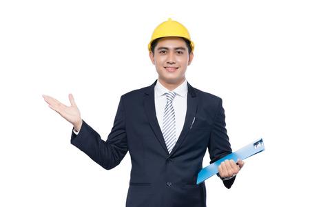 クリップボードとジェスチャを保持しているヘルメットとの若手建築家の男
