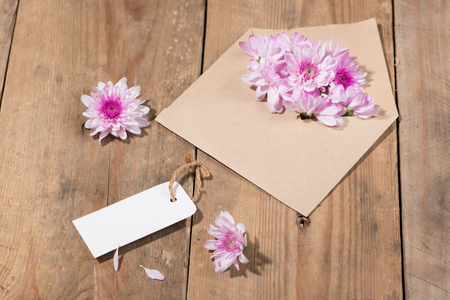 Blank white paper tag with brown envelope and pink flowers on wooden table.