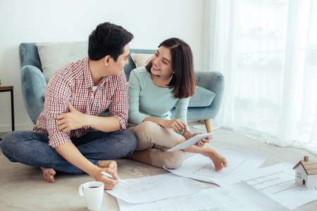 Attractive young asian adult couple looking at house plans. Stock Photo