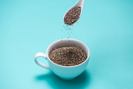 Cup of healthy chia seeds and spoon. Text space.