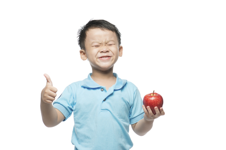 Asian baby boy holding and eating red apple, isolated on white Stock Photo