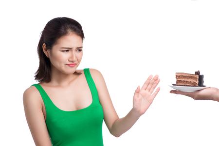 Het droevige gezicht van Aziatische jonge vrouw houdt van geen cake die op witte achtergrond wordt geïsoleerd.