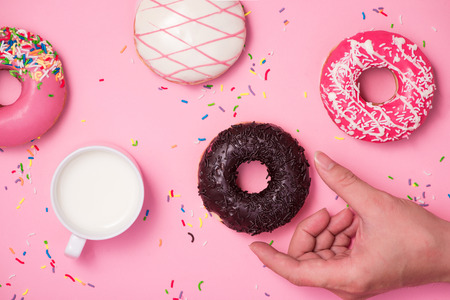 Donuts, sweetmeats candy on pink background. Hand holds donut. Stock Photo