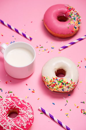 Donuts with icing and milk on pastel pink background. Sweet donuts. Stock fotó