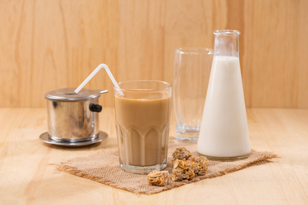 Coffee with milk on a wooden table.