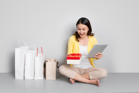 Woman shopping online at home sitting besides row of shopping bags holding red gift box.