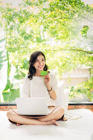 Beautiful asian womon holding a credit card and purchasing online Stock Photo - 83865424