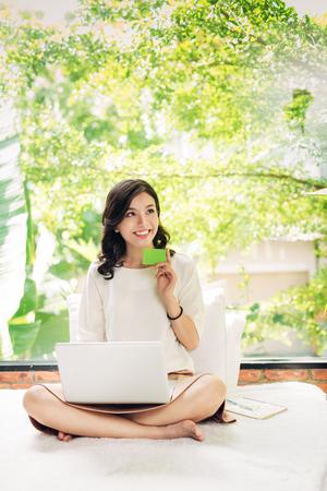 Hermosa asiática womon sosteniendo una tarjeta de crédito y comprando online Foto de archivo - 83865424
