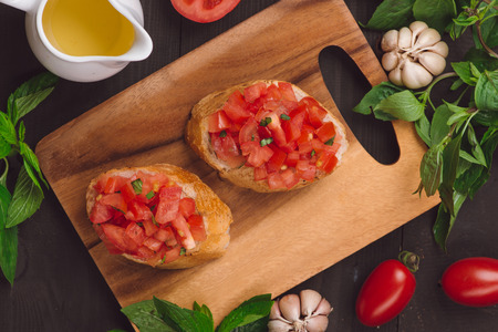 Appetizer bruschetta with tomatoes, olives and herbs. Italian cuisine