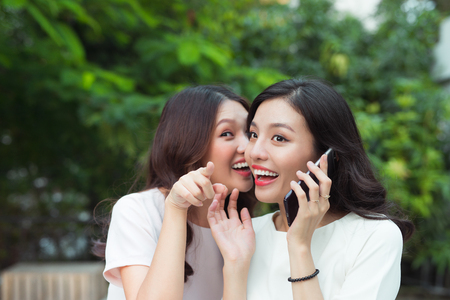 Young woman whispering into cheerful friend's ear while on call Stock Photo