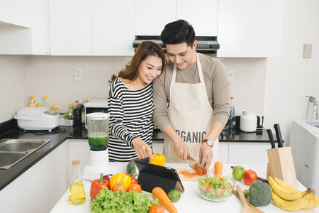 Young asian couple chopping vegetable and using digital tablet in the kitchen Imagens