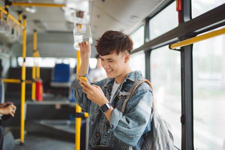 도시 버스에 앉아 하 고 전화에 메시지를 입력 잘 생긴 아시아 사람. 스톡 콘텐츠