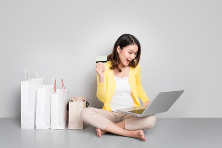 Jonge Aziatische vrouw winkelt online thuis thuis naast rij boodschappentassen