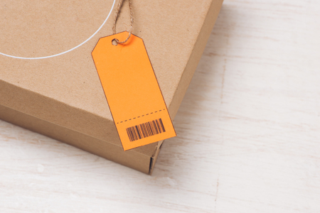 Parcel tied with string with address orange label attached 版權商用圖片