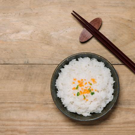 クローズ アップでご飯の木製ボウルに木製のテーブルの上