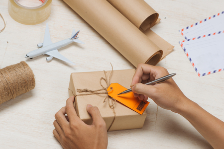 Male hand writing on luggage tag on brown paper parcel