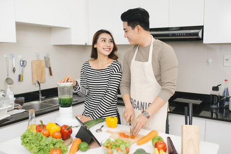Happy asian couple have fun in modern kitchen indoor while preparing fresh fruits and vegetables food salad