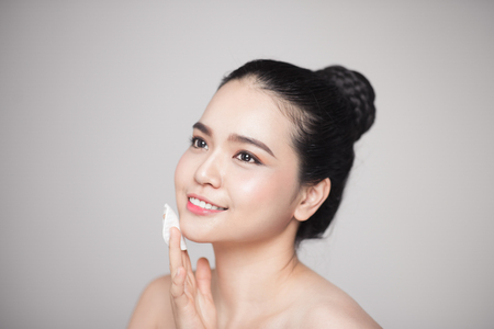 Happy smiling beautiful asian woman using cotton pad cleaning skin. Stockfoto
