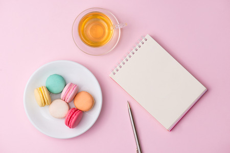 Flatlay of notebook, cake macaron and cup of tea on pink table. Beautiful breakfast with macaroon.