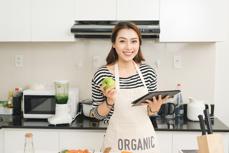 Young asian woman using a tablet computer to cook in her kitchen Standard-Bild
