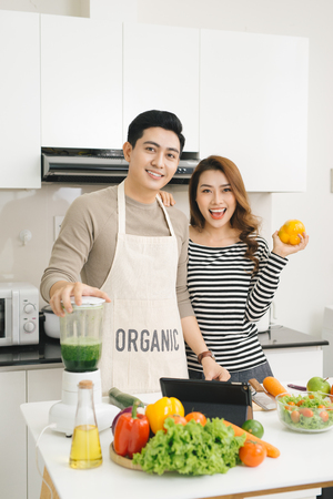 Happy asian couple in love in kitchen making healthy juice Imagens