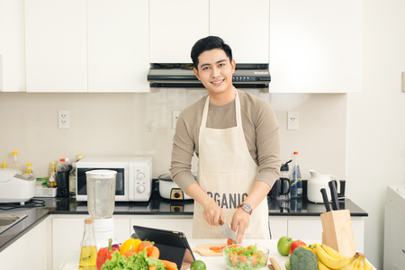 Young asian handsome man preparing food in kitchen at home Stock Photo