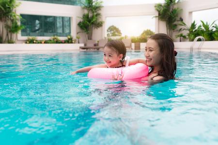 Moeder en babymeisje met plezier in het zwembad.