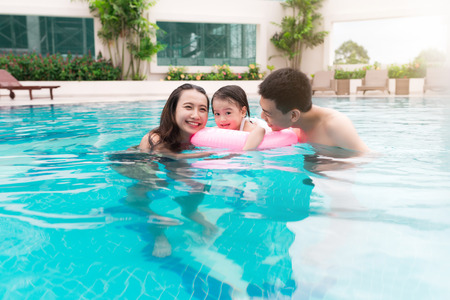 Happy family in swimming pool.