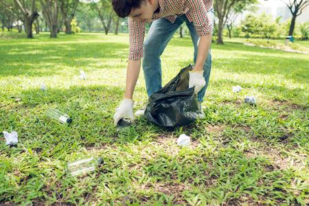 Asian man picking up plastic household waste in park Reklamní fotografie