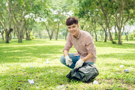 Young asian man holding black bin bag and putting plastic household waste into it Stock Photo