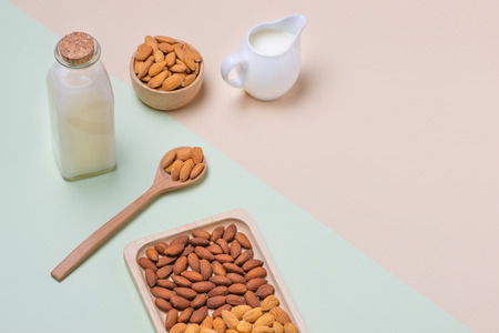 Almonds and milk bottle on light background. Almond nuts in spoon. 版權商用圖片