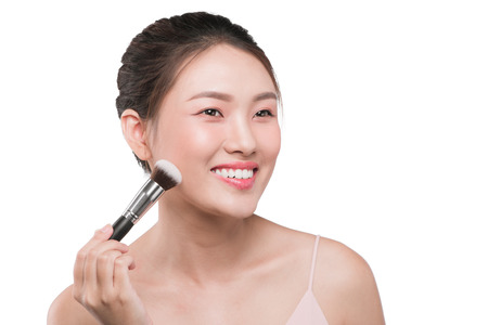 Portrait of attractive young asian woman holding make-up brushs over white