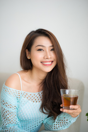 tea hot drink: Beautiful young asian woman drinking her morning tea over a breakfast at home.